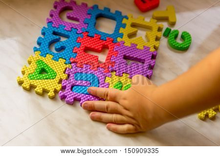 Colorful foam puzzle letters and numbers in kid's hands on a light table. Baby puts puzzle of letters and numbers. Close-up