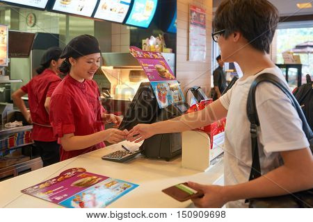SHENZHEN, CHINA - OCTOBER 22, 2015: woman ordering at the counter inside a McDonald's restaurant. McDonald's is the world's largest chain of hamburger fast food restaurants.