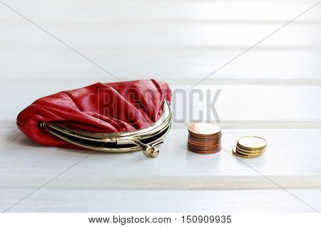 red retro purse and a stack of of coins on a light wooden background / money saving storage