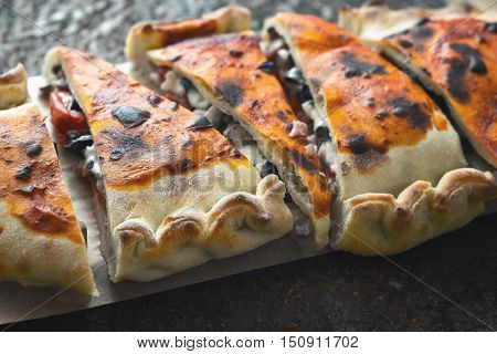 Sliced calzone on the stone background horizontal