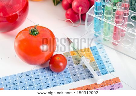 Tomatoes, Syringe, Test Tubes In Laboratory On Periodic Table. Gmo Conception