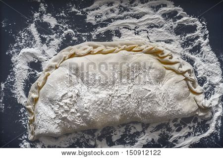 Raw calzone with flour on the dark background top view