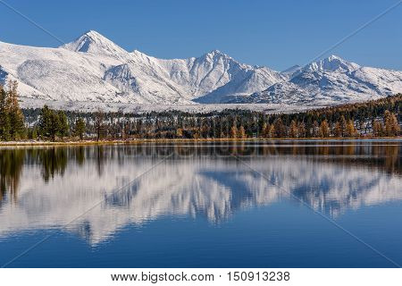 Bright picturesque autumn view with a beautiful lake forest snow covered mountains and their reflections on a background of blue sky on a sunny day