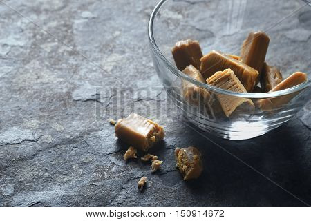 Toffee in the glass bowl on the stone table