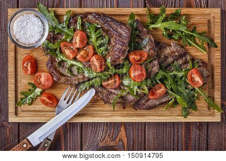 Steaks with arugula and tomatoes on dark wooden background top view.