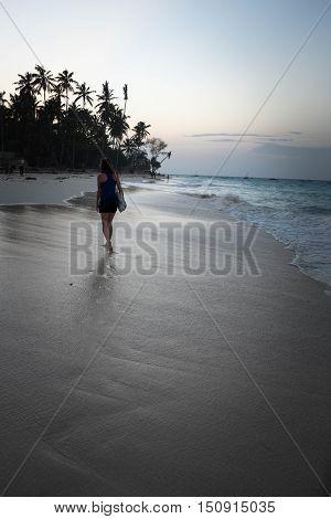Young girl with long hair walking across the ocean coast evening walk