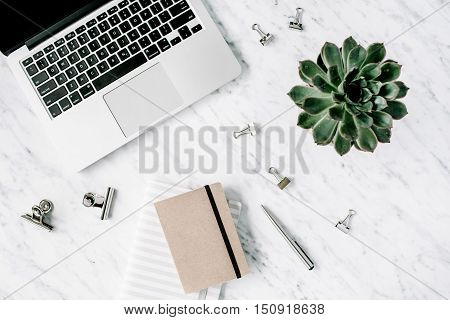 Flat lay top view office table desk. Workspace with laptop diary succulent and clips on marble background.
