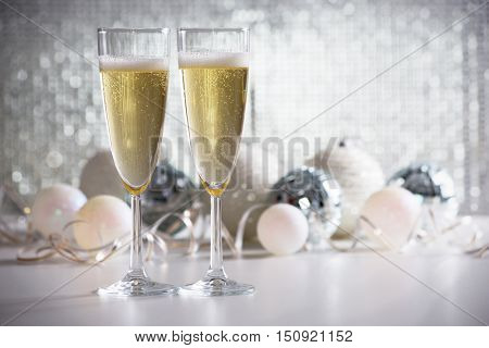 Champagne glasses and christmas balls on the bright background