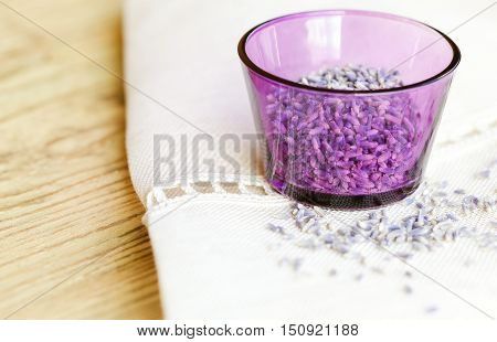 Dried lavender flowers in a purple glass on fabric and wood. Lavandula angustifolia with pale purple flowers used as culinary herbs and for essential oil extractions. Isolated macro photo close up.