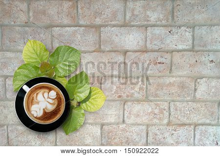 coffee and green leaves over brick wall as background
