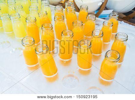 Fresh orange juice and pineapple juice in bottles glass.