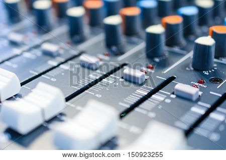 Regulators and mixer close-up controls. Shallow depth of field. Mixing console. Sound mixer. Live and studio equipment