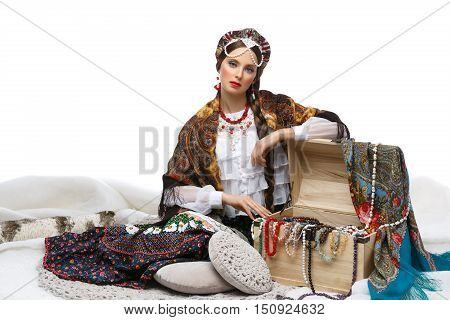 Beautiful young woman in traditional Russian clothes sitting near hope chest with colorful natural stone beads and shawl. Studio shot over white background.