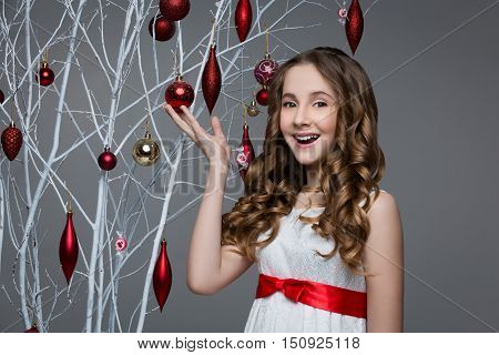 Beautiful teen girl with long curly hair in white dress with red ribbon belt standing near white tree branches wiht christmas decorations hanging on it. Studio shot on grey background. Copy space.