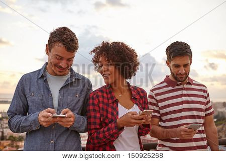 Three Friends Looking At Cell Phones