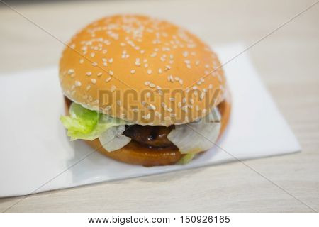 pork burger with lettuce on a sesame seed bun