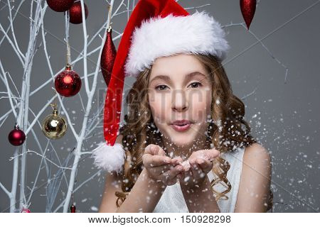 Beauiful girl in red santa cap blowing snow off palms of hands. Happy expression. Studio shot on christmas ornament background. Copy space.