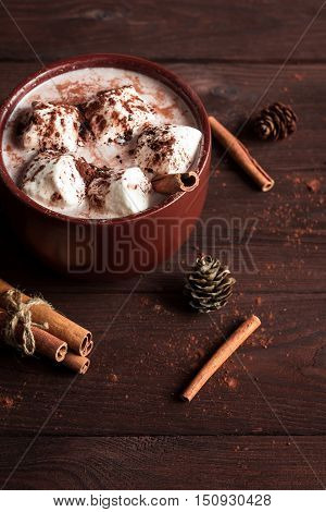 Christmas drink. Hot chocolate in a mug marshmallows cinnamon sticks and fir cones close-up