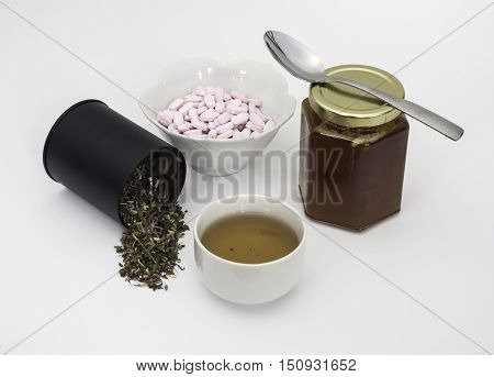 Green herb tulse with cup of tea Vitamin B12 tablets and jar of chestnut honey