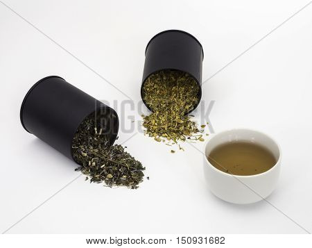 Two canisters of herbs spilling onto background with a cup of tea