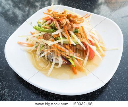 Green Papaya Salad (Som tum Thai) on table.