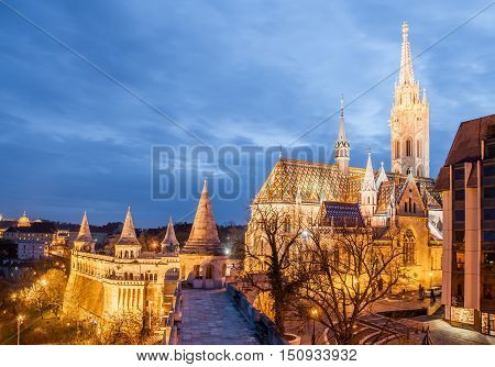 Night view of the Matthias Church is a Roman Catholic church located in Budapest Hungary in front of the Fisherman's Bastion at the heart of Buda's Castle District.