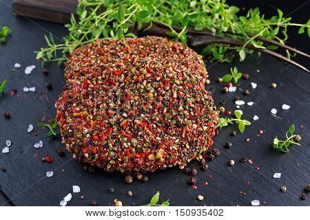 Raw peppered ground beef meat cutlets for burgers.