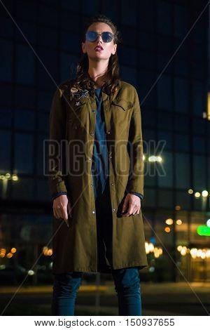 Beautiful woman standing on illuminated street at night.
