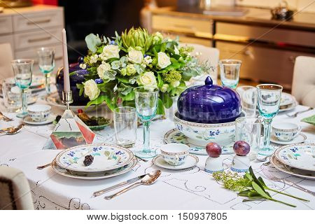 Decorated table ready for dinner. Beautifully decorated table set with flowers, candles, plates and serviettes for wedding or another event in the restaurant.