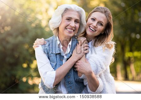 Two generation. Pretty satisfied mother and daughter smiling and hugging while having a walk in the park.
