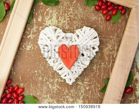 Frame with freshly picked berries and shapes of heart