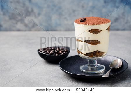 Tiramisu, traditional Italian dessert in glass on a grey stone background Copy space.