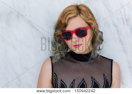Portrait of woman with red sunglasses and angled bob multicolored two-toned curly hair against marble background