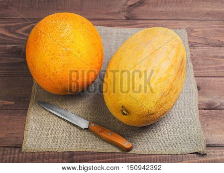 Two fresh ripe melon on a wooden table on sackcloth. Melon varieties Farmer melon varieties torpedo knife.
