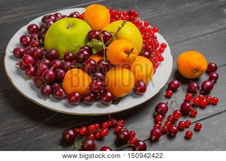 White plate with an assortment of fresh garden fruits and berries. Fruits apricot apple pear. Berries red currants cherries gooseberries. On dark black wooden table fruit and gooseberries apricots red currants cherries.