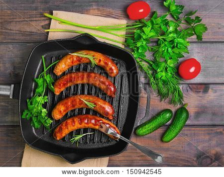 Grilled fried sausages kupaty on a cast iron skillet grill greens to grilled fried sausages parsley thyme rosemary tomatoes cucumbers. Fork for fried sausages. Grey wooden background. Top view.