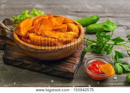 Baked potato wedges in wooden bowl board. Greens for baked potato wedges parsley fresh lettuce cucumber tomato ketchup. Slice Baked potato wedges dipped in ketchup. Gray wooden background rustic.