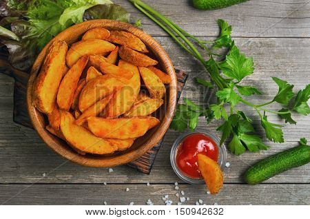 Baked potato wedges in wooden bowl board. Greens for baked potato wedges parsley fresh lettuce cucumber tomato ketchup. Slice Baked potato wedges dipped in ketchup. Gray wooden background rustic. Top view