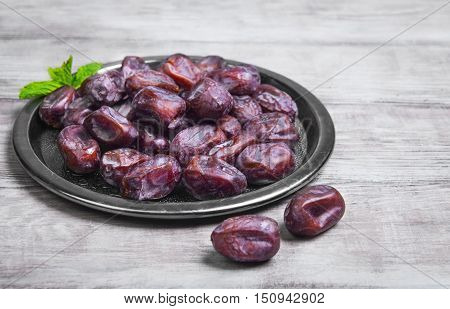 Side view of metal plate of Tunisian pitted dates mint. Dried dates on wooden white table top background