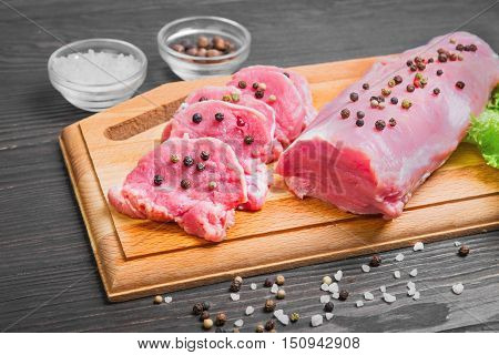 Raw meat pork tenderloin on cutting board ready to cook pork tenderloin cut into pieces of medallions. Seasonings for pork tenderloin fresh lettuce pepper salt. Dark brown wooden background.