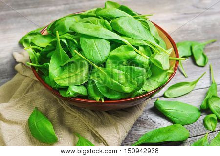 Fresh green leaves mini spinach in ceramic bowl. Spinach leaves on the gray wooden rustic background.