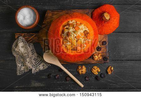 Pumpkin risotto with raisins. Rice porridge with sweet pumpkin raisins nuts. Baked pumpkin Halloween for rice. Sugar dark wooden background. Top view