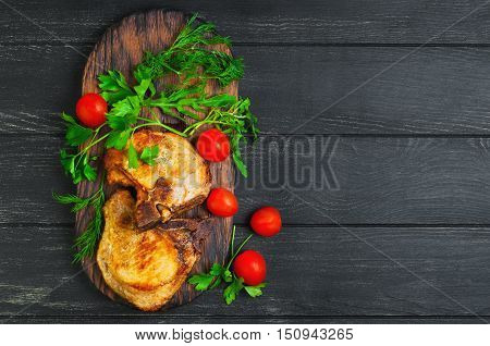 Grilled meat pork chops served in grill board ingredients for meat pork chops dill parsley lettuce cherry tomatoes dark black wood background top view