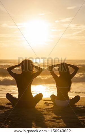 Two relaxed sexy young women or girls wearing bikinis sitting on a deserted tropical beach at sunset or sunrise