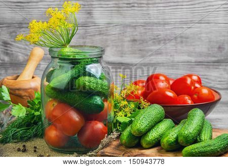 Preserving pickled cucumbers and tomatoes herbs for canning preserving rosemary dill parsley pepper onion. Fresh vegetables for Preserving tomatoes and cucumbers gray wooden background.