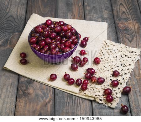 Ripe red purple berry gooseberries in purple bowl on gray wooden table. Gooseberry berries on the table cloth.