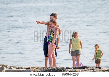 Wellfleet, USA - July 30, 2014: Two children siblings with boy pointing and holding hugging girl by Cape Cod ocean