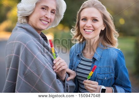 Like in childhood. Charming beautiful mother and daughter smiling and holding lollypop while having a walk.