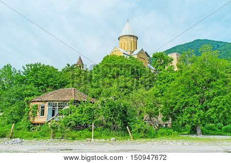 The dome of Assumption Church of Ananuri fortress rises from the lush greenery seen from the bank of Aragvi River Mtskheta-Mtianeti Region Georgia.