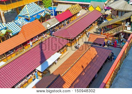 MOSCOW RUSSIA - MAY 10 2015: All the stalls of Izmailovsky Market are hidden under the red roofs protecting from sun rain and snow on May 10 in Moscow.